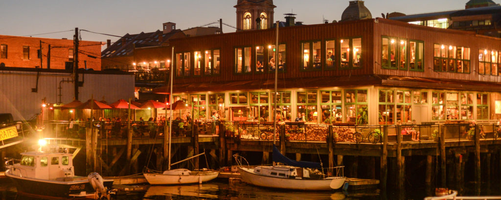 outdoor nighttime shot of portland maine waterfront with outdoor dining and boats out front