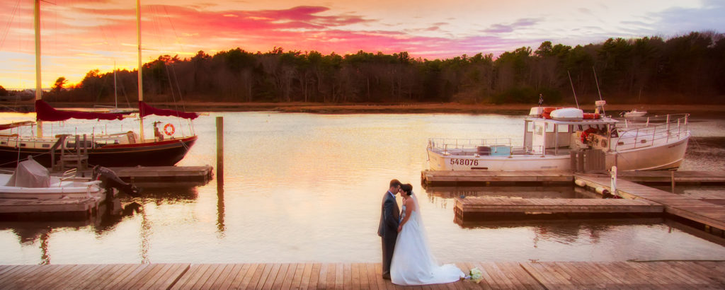 couple on dock in front of water and sunset