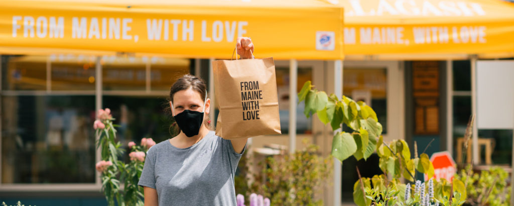 Woman holding up bag saying 'from Maine with love' while wearing mask, Photo Courtesy of Allagash Brewing and their staff