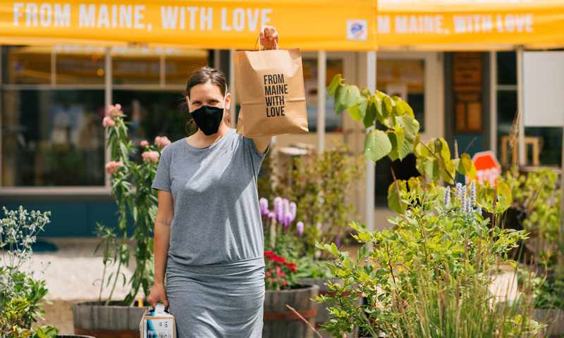 Woman holding up bag saying 'from Maine with love' while wearing mask, Photo Courtesy of Mat Trogner, via Allagash Brewing