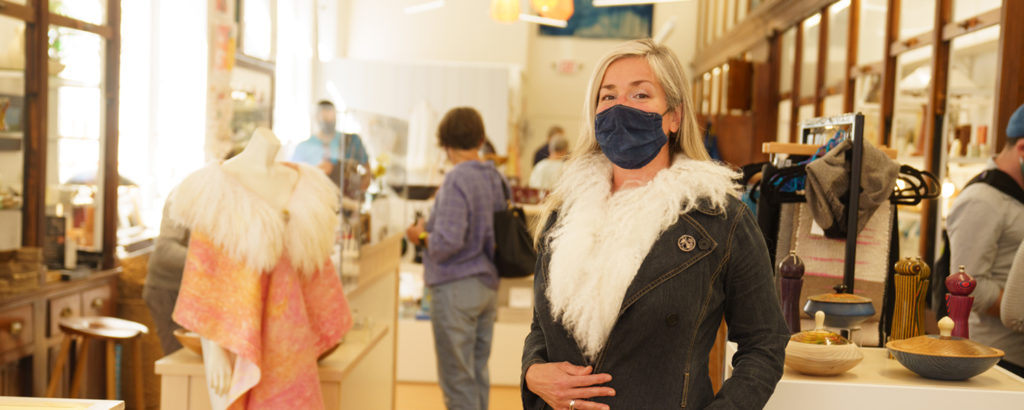Woman in mask trying on coat at Maine Craft Portland, Photo Courtesy of Good Maine