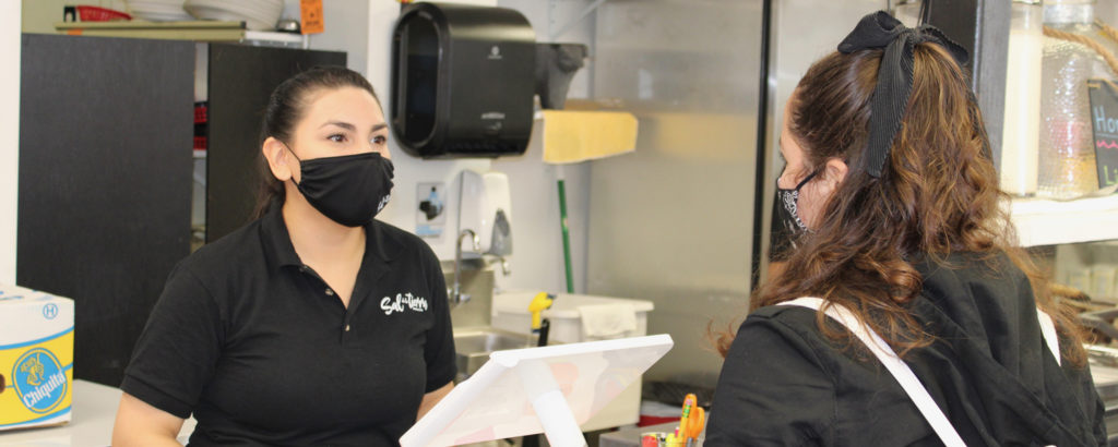 Customer and server in masks at Sal De La Tierra, Photo Courtesy Adam MacDonald