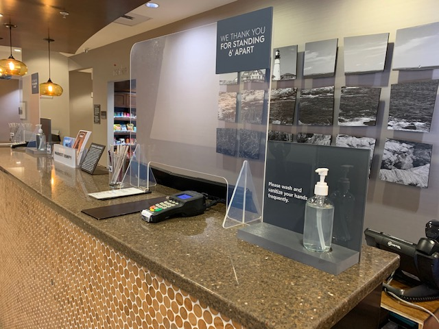 Front desk with protective barrier and sanitizer, Photo Credit: Residence Inn Portland Downtown Waterfront
