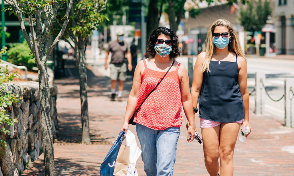 Two women wearing masks in Freeport, Maine and carrying shopping bags, Photo Credit: Sharyn Peavey Photography